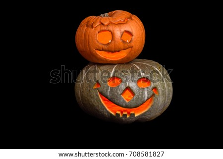 Two stacked Halloween pumpkins with smiley faces on black background