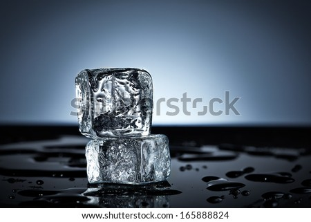 Two stacked ice cubes on wet black surface - stock photo