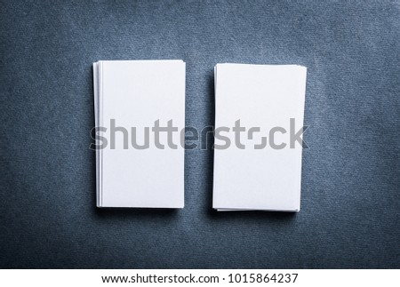 Two stacks of blank paper business cards on textured background.