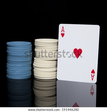Two stacks of blue and white poker chips with an ace of hearts card reflected on a shiny black surface