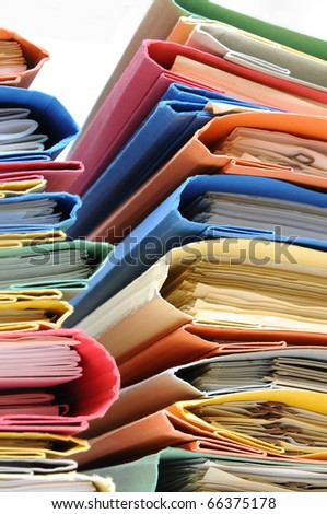 Two stacks of colorful office folders with documents - stock photo