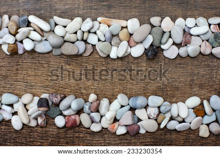two stacks of colorful stones with a parallel position on background wood texture - stock photo