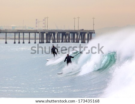 Two stand-up paddlers riding a large wave by a pier. - stock photo