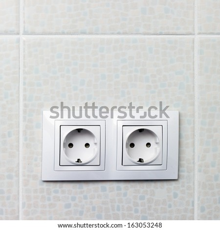 Two standard sockets on white wall - stock photo