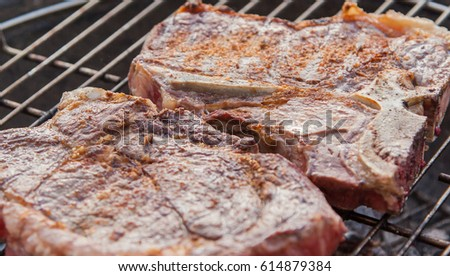 Two steaks on bowl grill in front of pool