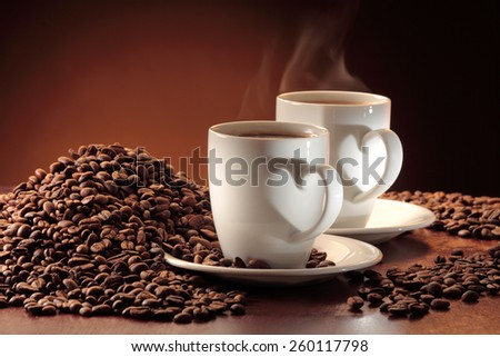 Two steaming  cups of coffee and a heap of coffee beans - stock photo