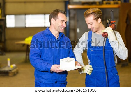 Two steel construction workers with angle grinder inspecting metal pieces