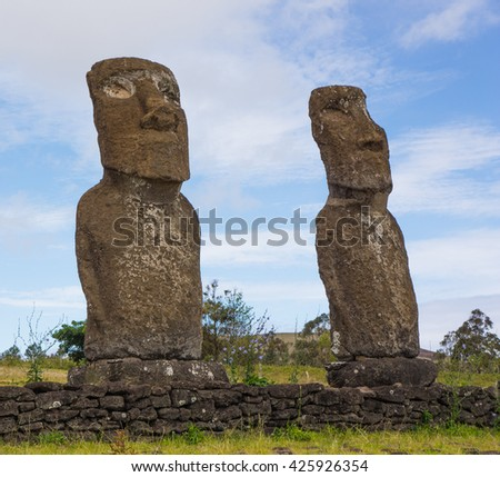 Two stone Easter Island ancestor statues keep watch in a grassy field with blue sky and white clouds