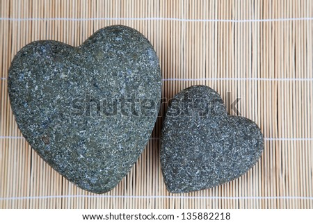 two stone hearts on a bamboo mat