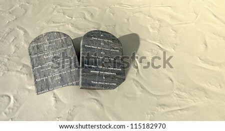 Two stone tablets with the ten commandments inscribed on them lying on brown desert sand - stock photo