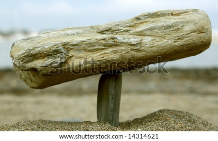 two stones in equilibrium, sand beach background - stock photo