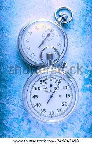 Two stopwatches on textured background in toning - stock photo