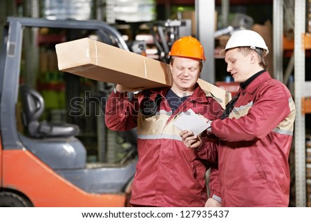two store workers man in uniform in front of warehouse forklift loader discussing order