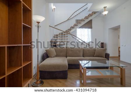 Two-storey studio apartment. Interior. A wooden staircase. - stock photo
