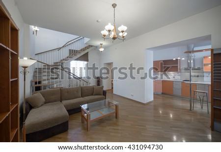 Two-storey studio apartment.  Kitchen.  A wooden staircase. - stock photo