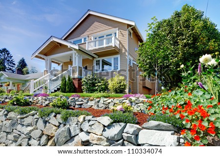 Two story beige nice house on the hill with rock walls and flowers. - stock photo