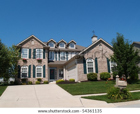 Two story brick home with window boxes and garage. - stock photo