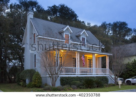 Two story house lit up at twilight - stock photo