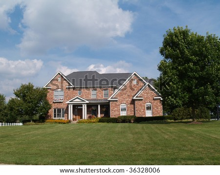 Two story large brick residential home with flower box.