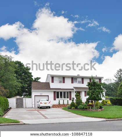 Two Story Ranch Style Home double wide Driveway with parked car in Suburban Neighborhood sunny blue sky day - stock photo