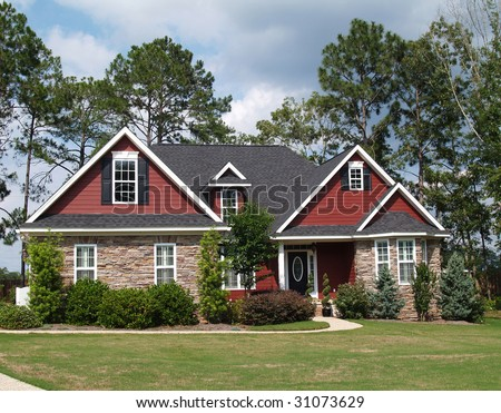 Two story residential home with both stone and board siding on the facade. - stock photo