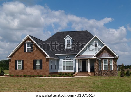 Two story residential home with brick, stone and board siding on the facade. - stock photo