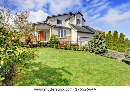 Two story siding house with brick trim, column porch and garage. Green lawn with trimmed hedges, fir trees and flourishing trees