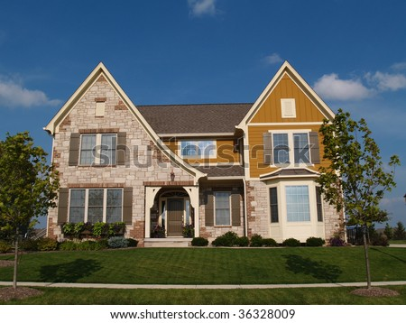 Two story stone, brick and board sided residential home with bay window. - stock photo