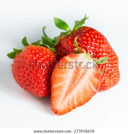 Two strawberries and a half on a white background - stock photo