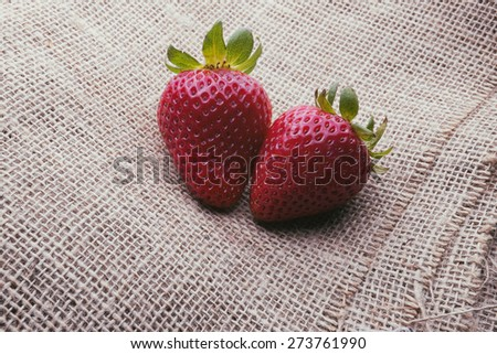 Two strawberries on a burlap background - stock photo