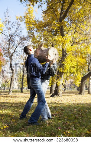 two strong men lifting logger in autumn fall park  - stock photo