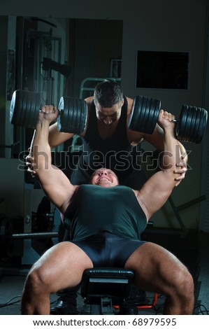Two strong muscullar mans training body in gym. - stock photo
