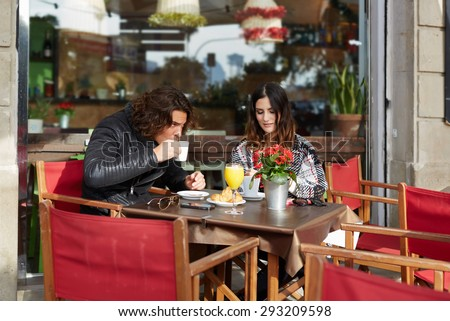 Two student friends drinking cafe after university classes in a restaurant terrace outdoors at cold spring day while they enjoying warm tea and a delicious cake, young couple breakfast in coffee shop - stock photo