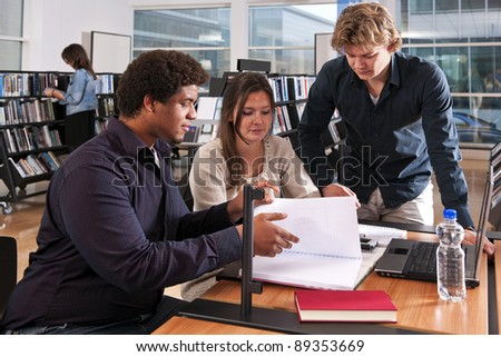 Two students and a tutor working on a project inside a public library, where a woman is browsing through books in a bookshelf - stock photo