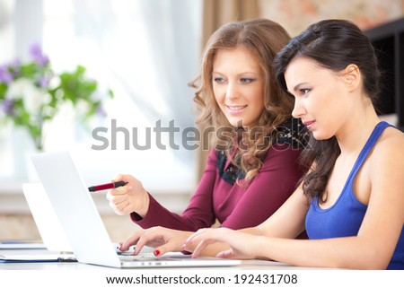 two students in class, two young woman with computers - stock photo