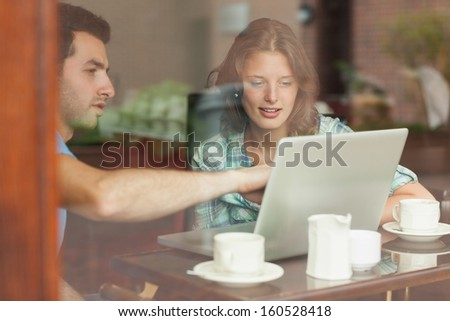 Two students looking at laptop in college canteen - stock photo