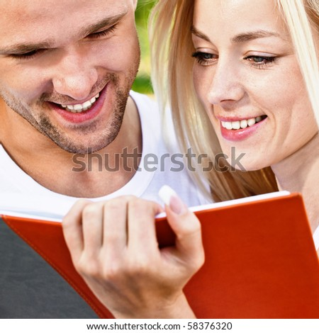 Two students read textbook against summer nature. - stock photo
