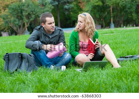Two students relax and talking on the grass in the park