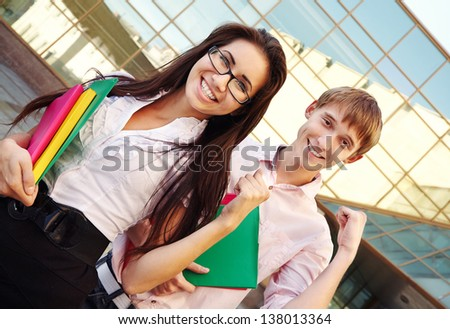 Two students showing success near school - stock photo