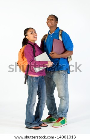 Two students stand and look at  each other with happy expressions on their faces. They wear backpacks and he carries a notebook. Vertically framed photograph. - stock photo