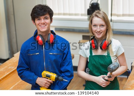 Two students standing in a woodwork class while holding a driller and a hammer - stock photo
