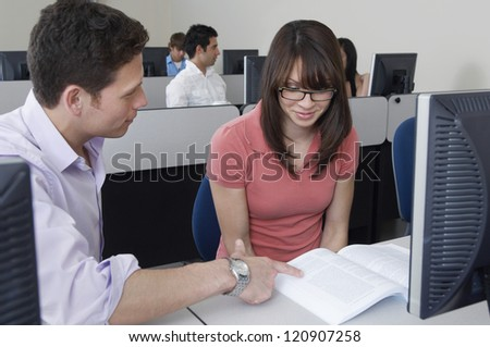 Two students studying in front of monitor in classroom
