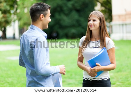 Two students talking outdoor - stock photo