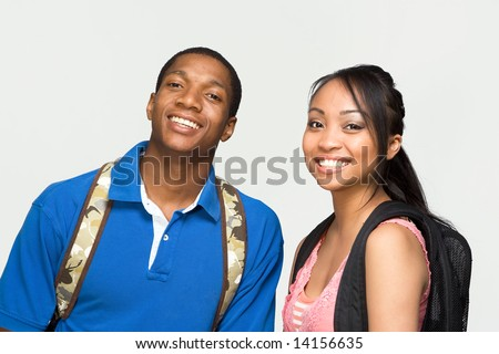 Two students wearing backpacks are laughing. Horizontally framed photograph