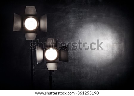 Two studio light source with reflectors are on the chalk board background - stock photo