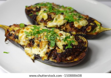 two stuffed aubergines, stuffed with minced meat, and cheese - stock photo