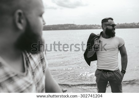 Two stylish bearded men on the background of the lake - stock photo