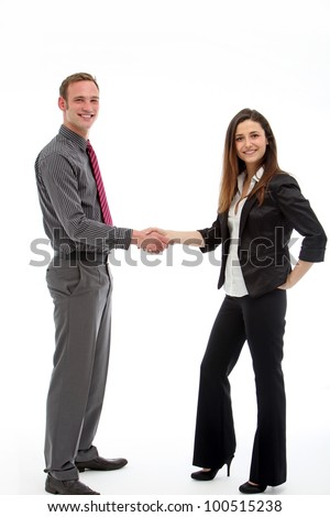 Two stylish business executives stand shaking hands at the conclusion of a successful business dea - stock photo