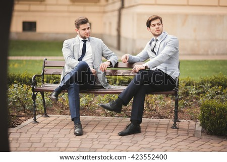 Two stylish businessmen speaking and smiling outdoors - stock photo