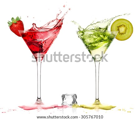 Two stylish cocktail glasses with fruity liquor splashing out, garnished with a ripe fresh strawberry and kiwi, closeup isolated on white. Party concept. - stock photo